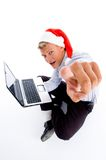 Pointing man with christmas hat and laptop Stock Photo