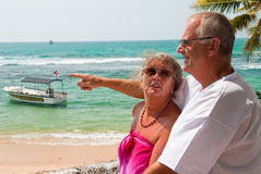 Pointing mature couple by ocean. Mature couple together next to the beach. In the background turquoise blue water from the ocean can be seen, tropical scenery Stock Photography