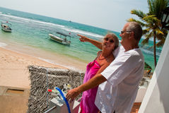 Pointing mature couple by ocean. Mature couple together next to the beach. In the background turquoise blue water from the ocean can be seen, tropical scenery Stock Photo