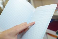 Pointing at notebook ou schoolbook Stock Photos