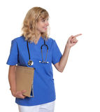 Pointing nurse with blond hair and file Stock Photos