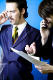 Pointing out error in work. Two businessmen talking on their cellphones, trying to resolve an error found in the contract they are holding royalty free stock photos