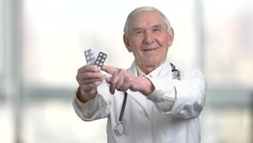 Pointing at the pack of medicine pills. Smiling very old doctor recommed pills to you in hospital, bright blurred background stock video