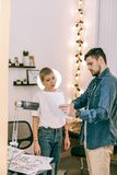 Female tattoo master with boyish haircut attentively looking on picture. Pointing on page. Female tattoo master with boyish haircut attentively looking on stock photo