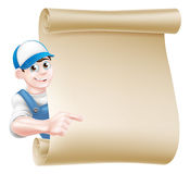 Pointing plumber scroll. A pointing cartoon mechanic, plumber, handyman, decorator or gardener leaning around a scroll and pointing at a message on it Royalty Free Stock Photography