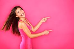Pointing showing woman excited. Excited girl pointing showing at pink background with copy space. Young beautiful happy smiling and laughing woman of mixed Stock Image