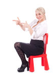 Pointing, sitting on child's chair young woman Royalty Free Stock Images