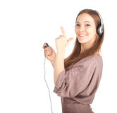 Pointing smiling girl in headphones Stock Image