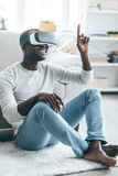 Pointing somewhere. Handsome young African man in smart casual clothes pointing somewhere and smiling while sitting on the carpet at home Stock Photos