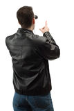 Pointing Spectator. A rear view of a spectator wearing a leather jacket, and pointing at something, isolated against a white background Royalty Free Stock Photos