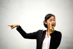 Pointing and telling. Asian business woman pointing onto something or someone and at the same time telling secretly to others. portrait concept of office life/ royalty free stock photography