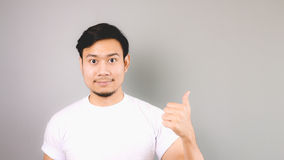 Pointing with thumb or the first step hand sign. An asian man with white t-shirt and grey background royalty free stock photography