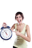 Pointing The Time. Expressive Young Woman Holding A Big Alarm Clock And Pointing The Time Royalty Free Stock Image