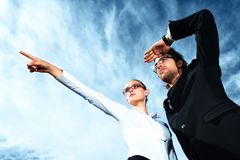 Pointing to aim. Successful business people  standing over blue sky and purposefully looking away Stock Photography