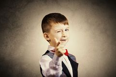 Pointing to camera funny little boy with one eye closed isolated. Over yellow background stock images