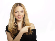 Pointing to the right. Pretty blond woman pointing to her left, over white Stock Photography