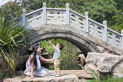 Pointing to the Sky. A Chinese mother watches her son as he points at a passing bird high in the sky beside a bridge Stock Images