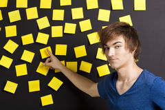 Pointing to a yellow note. Young student pointing to a board full of yellow notes and looking in to the camera Stock Photography