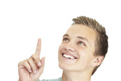 Pointing up. A smiling young teenager is pointing up Stock Image