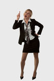 Pointing Up. Full body of an attractive blond woman wearing business suit with tie and skirt looking and pointing up with mouth open royalty free stock photos