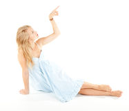 Pointing up beautiful girl in blue dress Royalty Free Stock Photos