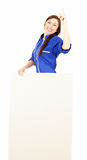 Pointing up young woman in overalls showing sign Royalty Free Stock Image