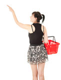 Pointing up young woman with red shopping basket Royalty Free Stock Image