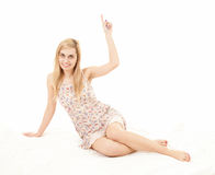 Pointing up young woman sitting on the floor Royalty Free Stock Images