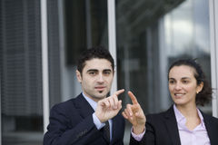 Pointing on a virtual screen. Two Businesspeople pointing on a virtual screen royalty free stock images