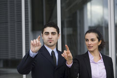 Pointing on a virtual screen. Two Businesspeople pointing on a virtual screen royalty free stock image