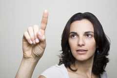 Pointing on a virtual screen. Young woman pointing on a virtual screen Royalty Free Stock Images