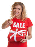 Pointing woman with blond hair and gift in a sales-shirt Stock Image