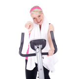 Pointing woman exercising on stationary bicycle Stock Photography