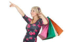 Pointing woman keeping coloured shopping bags Stock Photography