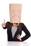 Pointing woman in sad ecological paper bag on head Royalty Free Stock Image