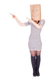 Pointing woman in smiling paper bag on head Royalty Free Stock Photo