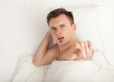Pointing you irritated young man in bedding Stock Images