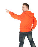 Pointing young man in orange sweatshirt Stock Images