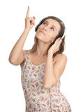 Pointing young woman in headphones Stock Image