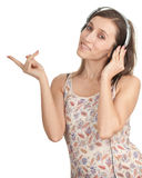 Pointing young woman in headphones Stock Photo