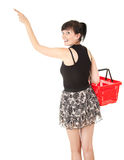 Pointing young woman with red shopping basket Stock Photos