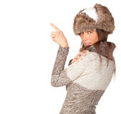 Pointing young woman in white winter hat Royalty Free Stock Photos