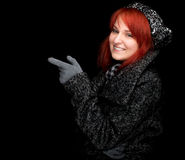 Pointing young woman in winter clothes Royalty Free Stock Images