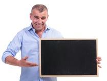 Points d'homme âgés par milieu occasionnel au tableau noir Images libres de droits
