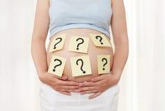 Points d'interrogation sur le ventre du ` s de femmes Photographie stock libre de droits