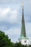 Pointy church spire. Very pointy church steeple with a cross, a clock and copy space royalty free stock images