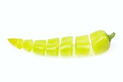 Pointy green pepper cut in pieces. On white background stock photos