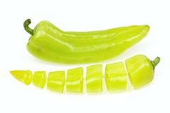 Pointy green pepper and one cut into pieces. On white background royalty free stock photography