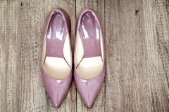 Pointy patent pumps in old pink color on wooden floor. Pointy patent female wedding heels in old pink color, placed on a wooden floor, view from above stock images