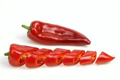 Pointy red pepper and one cut into pieces. On white background royalty free stock image